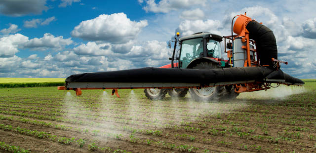 farmer spraying gmo